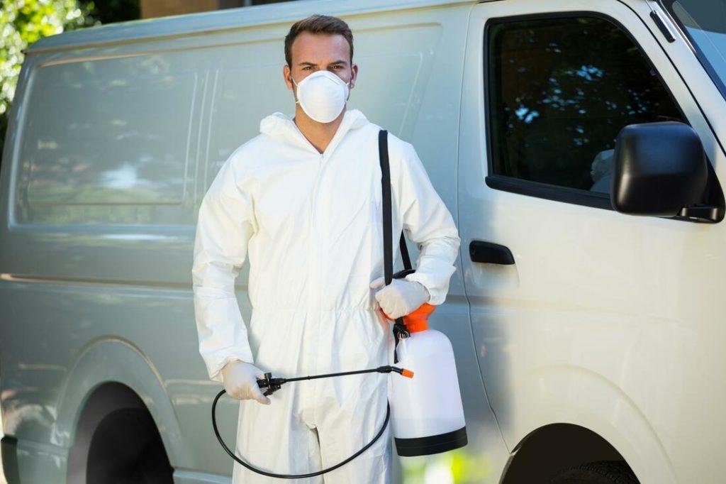 A pest control expert standing beside a car